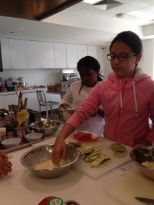 Imari and Olivia cover the vegetables in flour and egg to be cornmeal crusted.